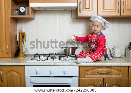 Little cook adds salt to the soup - stock photo