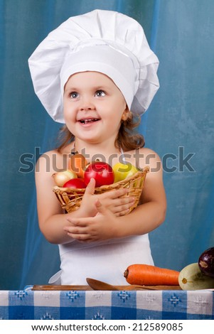Little cook prepares healthy food, cheery kitchen boy at the table, cheery kitchen boy holding a basket of vegetables