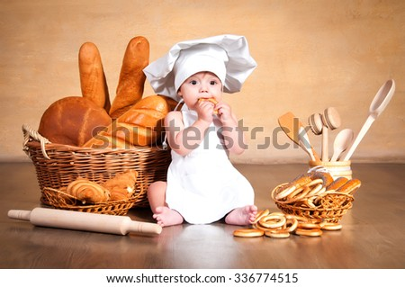 Little cook. Small kid in a chef's hat with wicker baskets of pastries, rolls, bread and bagels - stock photo