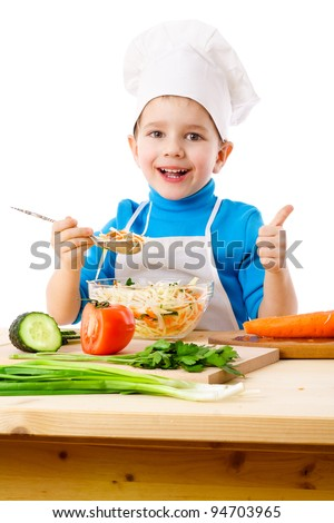 Little cook tasty salad and showing thumb up sign, isolated on white