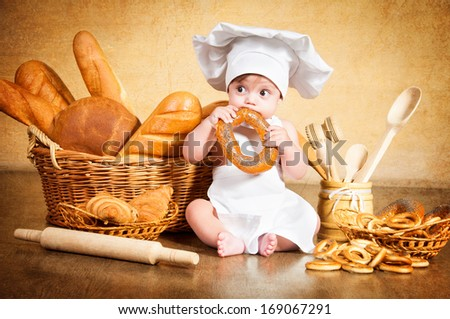 Little cook with a bagel in her hands. - stock photo