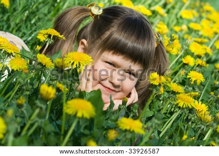 Little cool smiling girl is lying on the flowering dandelion meadow - stock photo