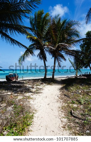 LITTLE CORN ISLAND, NICARAGUA: A sandy path leads to a deserted, tropical, white sand beach and an abandoned fishing boat. - stock photo