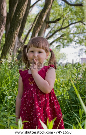 Little country girl in the woods making sing of silence looking at you with smile