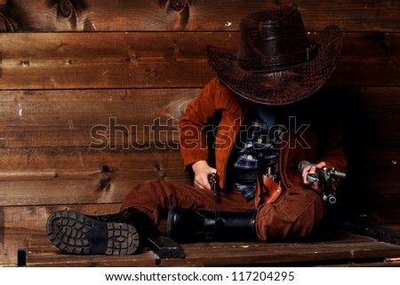 little cowboy sittng on wooden box near wall and holding pistols - stock photo