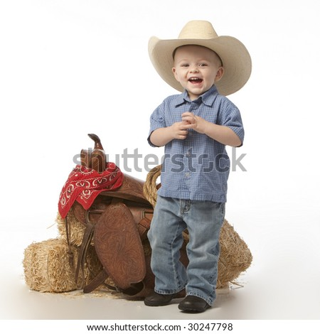 Little cowboy with saddle - stock photo