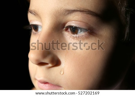 Little crying boy on black background, close up view
