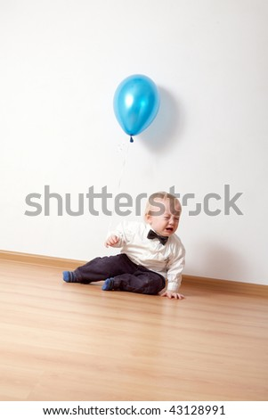 little crying boy with balloon - stock photo