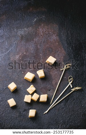 Little cubes of Belgian cheese with cocktail sticks over black background. Top view. - stock photo
