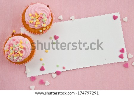 Little cupcake with frosting and colorful sprinkles on pink - stock photo