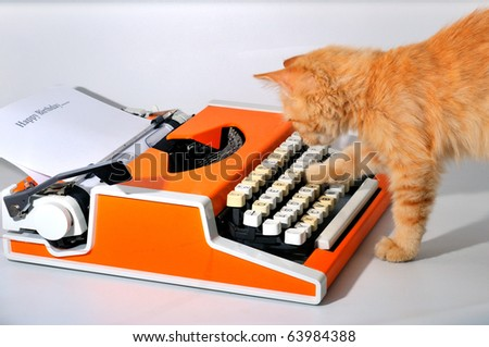 Little curious, ginger kitten playing with a machine for printing - stock photo