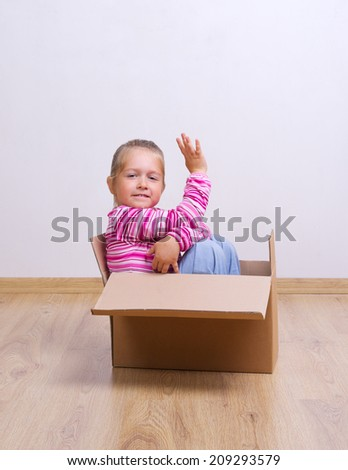 Little curious girl in a box - stock photo