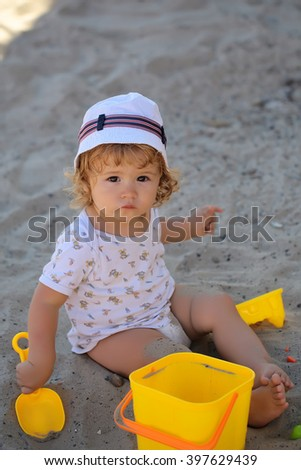 Little curious smart blonde baby boy in hat sitting on sand outdoor playing with plastic colorful toys on natural beach background, vertical picture - stock photo