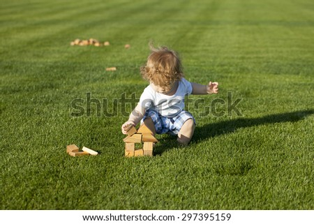 Little curly baby boy sat down to build toy wooden house on the green lawn sunny day outdoor, horizontal photo - stock photo