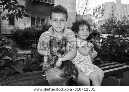 Little curly boy and a girl sitting on a bench and holding a dog in her arms. Black and white photo.
