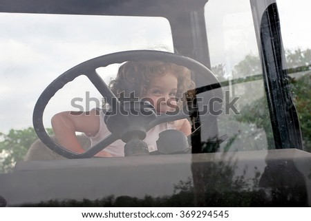 Little curly girl emotionally hold on to the steering wheel in the tractor cab - stock photo