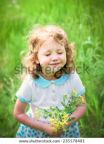 Little curly girl with closed eyes and a bouquet of wildflowers, soft focus - stock photo