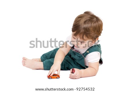 Little cut boy playing with two toy cars. Isolated on white.