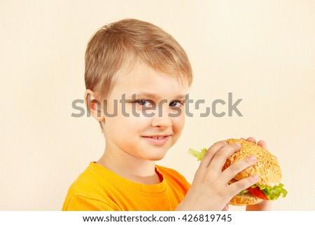 Little cut boy with a tasty sandwich - stock photo