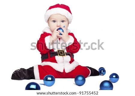 little cute baby boy Santa Claus chews blue Christmas ball on white background - stock photo