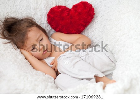 Little cute baby boy with a red heart, sleeping and resting - stock photo