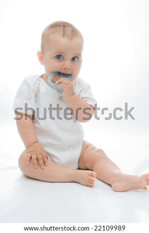 little, cute baby boy with teether on bright background