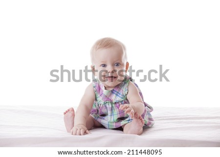 Little cute baby-girl in dress, sitting, isolated - stock photo