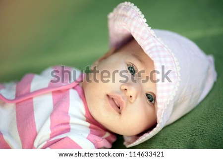 Little cute baby girl in pink on green background looking to camera. - stock photo