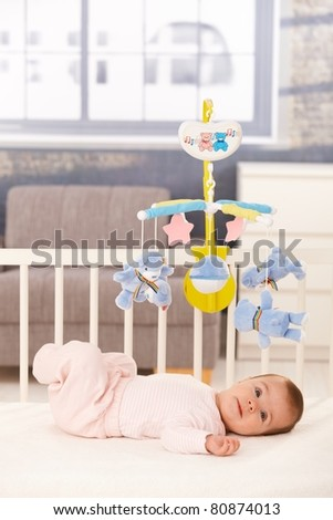 Little cute baby girl lying in crib with toy mobile.? - stock photo