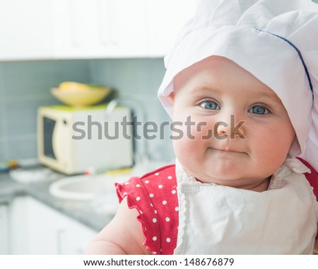 little cute baby in a chef's hat in the kitchen - stock photo