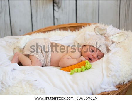little cute baby in a rabbit suit. laying in the basket - stock photo