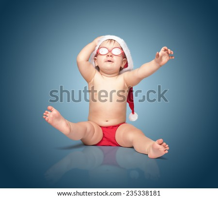little cute baby in red Santa hat and red glasses barely holds his hat, surprise! sits on a colored background. - stock photo
