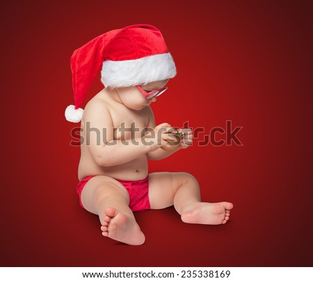 little cute baby in red Santa hat on color bacground - stock photo