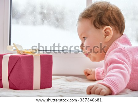 Little cute baby looking at the gift box