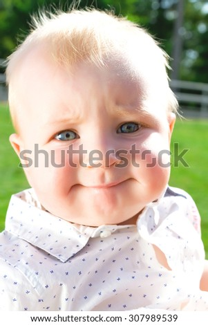 Little cute baby outdoor.A cute child outside on a grass field (copy space).Adorable toddler boy in the park.Summer portrait of happy baby girl infant outdoors at park.Baby wearing white shirt. - stock photo
