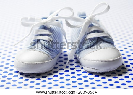 Little cute baby shoes on a blue pattern