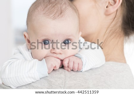 Little cute baby with big blue eyes sucking his little fist in mouth. Lying on mother's arm