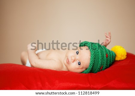 little cute baby with christmas tree hat on red background - stock photo