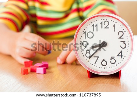 Little cute baby with clock at the table.