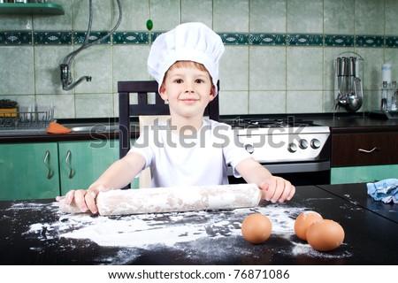 Little cute baker in kitchen - stock photo