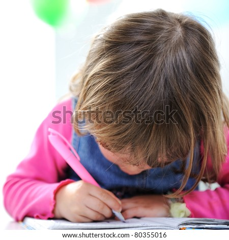 Little cute blond baby girl is drawing with pencil on paper - stock photo