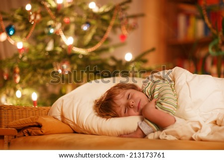 Little cute blond boy sleeping under Christmas tree and dreaming of Santa at home, indoors - stock photo