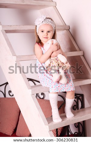 Little cute blond girl in dress sitting on wooden stairs with soft toy in her hands - stock photo