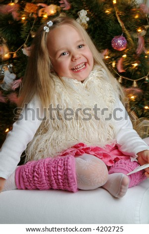 Little cute blond girl in front of christmas tree. - stock photo