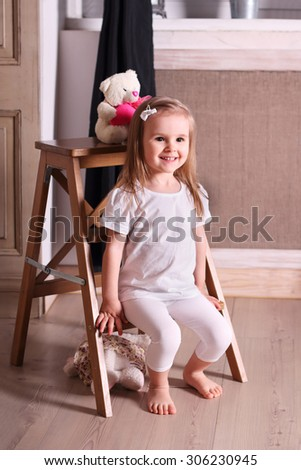 Little cute blond girl sitting on small wooden ladder in room with soft toys - stock photo