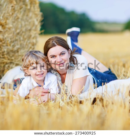 Little cute blond kid boy and his young mum on yellow hay field in summer. Happy family of two enjoying nature and togetherness. - stock photo