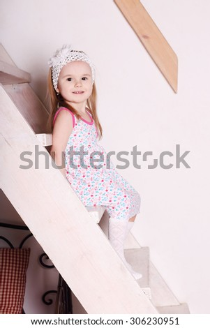 Little cute blond smiling girl in dress sitting on wooden stairs - stock photo