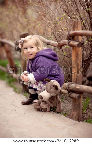 little cute blond smiling girl in the purple coat with hood is sitting near the fence with her toy wolf - stock photo