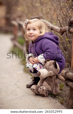 little cute blond smiling girl in the purple coat with hood is sitting near the wooden fence with her toy wolf - stock photo