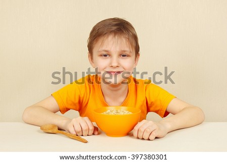 Little cute blonde boy is going to eat a porridge - stock photo